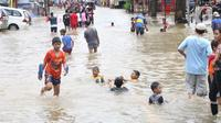 Anak-anak bermain di genangan air yang membanjiri Jalan KH Hasyim Ashari, Tangerang, Banten, Kamis (2/1/2020). Banjir yang menggenangi jalan penghubung Jakarta- Tangerang tersebut mulai surut dan sudah bisa dilintasi pejalan kaki. (Liputan6.com/Angga Yuniar)