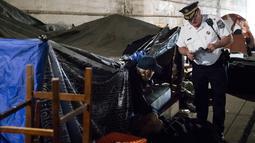 Seorang petugas polisi mengusir seorang pria yang tinggal dalam tendanya di bawah jembatan di Philadelphia (30/5). Selain itu tempat yang mereka tinggali menjadikan bagian kota terlihat kotor dan kumuh. (AP Photo/Matt Rourke)