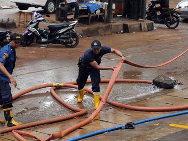 Petugas Damkar PB menarik selang pembuangan saat melakukan penyedotan di salah satu pertokoan di Jalan Kemang Raya, Jakarta, Minggu (28/8). Dua lokasi parkir bawah tanah pertokoan di kawasan Kemang terendam air. (Liputan6.com/Helmi Fithriansyah)