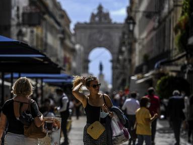 Orang-orang berjalan menyusuri jalan di depan lengkungan Rua Augusta di pusat kota Lisbon, Portugal, Senin (13/9/2021). Portugal hari ini mengakhiri aturan wajib penggunaan masker di jalan-jalan. (PATRICIA DE MELO MOREIRA / AFP)