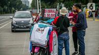 Pedagang kaos cendera mata keliling berinteraksi dengan wisatawan kawasan Monas, Jakarta, Sabtu (2/1/2021). Sejumlah tempat wisata dan taman terbuka yang dikelola Pemprov DKI ditutup selama hari Natal dan Tahun Baru. (Liputan6.com/Faizal Fanani)