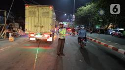 Petugas kepolisian mengatur arus lalu lintas di posko penyekatan mudik di Kedungwaringin, Kabupaten Bekasi, Senin (10/5/2021). Pada H-3 menjelang Idul Fitri 1442 H, jumlah petugas yang berjaga di pos penyekatan pemudik di Kedungwaringin, ditambah sebanyak 150 orang. (Liputan6.com/Herman Zakharia)