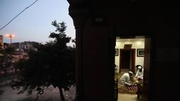 Umat Muslim berbuka puasa di Masjid Jama yang sepi, yang biasanya dipadati ribuan umat selama bulan suci Ramadan, karena penguncian nasional untuk mengendalikan penyebaran virus corona Covid-19, di New Delhi, India (25/4/2020). (AP Photo/Manish Swarup)