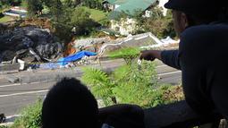 Warga melihat area longsor dari ketinggian di kawasan Ciloto, Cianjur, Jawa Barat, Kamis (29/3). Tebing di bahu Jalan Raya Puncak itu kembali mengalami longsor dengan kedalaman 40 meter dan panjang lebih kurang 150 meter. (Merdeka.com/Arie Basuki)