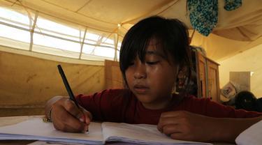 Dinar sedang mengerjakan tugas sekolah di tenda daruratnya di Kelurahan Balaroa, Palu Barat, Rabu (18/3/2020). (foto: Liputan6.com/Heri Susanto).
