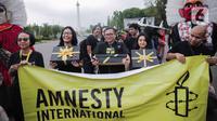 Aktivis yang tergabung dalam Amnesty Internasional Indonesia menggelar aksi di depan Istana Negara, Jakarta, Selasa (10/12/2019). Aksi tersebut digelar untuk memperingati Hari HAM Sedunia 2019. (Liputan6.com/Faizal Fanani)