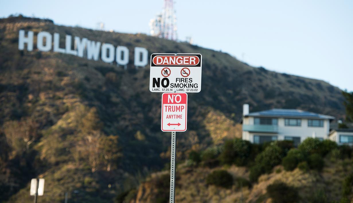 "Sebuah rambu bertuliskan ""No Trump Anytime"" terlihat di jalan utama dekat Bukit Hollywood, California, Rabu (27/4). Rambu anti-Donald Trump tersebut dibuat oleh seniman jalanan yang memiliki nama sebutan 'Plastic Jesus'. (Robyn BECK/AFP)"