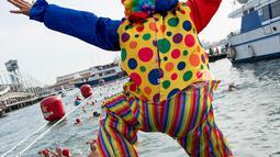 Seorang peserta dalam kostum badut melompat ke air saat  kompetisi renang Copa Nadal di Port Vell Barcelona, Selasa (25/12). Lomba renang tradisonal ini berlangsung pada hari natal sejak 1908 di pelabuhan tua Barcelona. (Josep LAGO / AFP)