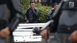 Anggota kepolisian dari satuan Brimob beristirahat saat menjaga aksi unjuk rasa yang dilakukan Gerakan Nasional Kedaulatan Rakyat di depan Gedung Bawaslu, Jakarta, Selasa (21/5/2019). Ribuan aparat keamanan gabungan diterjunkan untuk mengamankan jalannya aksi. (Liputan6.com/Helmi Fithriansyah)