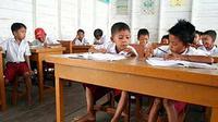 Sejumlah siswa sekolah dasar belajar di ruang kelas SDN 068009, tanpa memakai sepatu, di Desa Nelayan, Belawan, Sumut.(Antara)