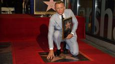 Daniel Craig berpose di atas bintang barunya di Hollywood Walk of Fame pada upacara penghargaan di Los Angeles, Rabu (6/10/2021). Nama Daniel Craig di Hollywood Walk of Fame diletakkan di samping aktor Roger Moore, pemeran James Bond terdahulu. (AP Photo/Chris Pizzello)