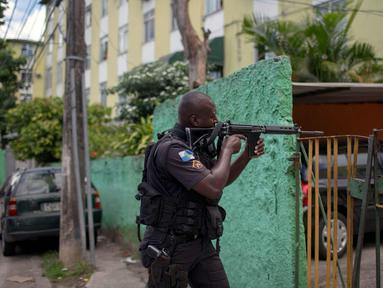 Seorang polisi militer melakukan operasi penggerebekan di daerah kumuh Cidade de Deus di Rio de Janeiro, Brasil (1/2). Daerah Cidade de Deus dikenal sebagai kampungnya para gembong dan penyelundup narkotika. (AFP Photo/Mauro Pimentel)