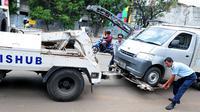 Petugas Dinas Perhubungan DKI Jakarta memasang alat derek untuk membawa mobil yang parkir di bahu jalan di kawasan Jatinegara, Jakarta, Senin (2/10). (Liputan6.com/Helmi Afandi)