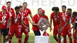 Pelatih kepala Bayern Munchen Hans-Dieter Flick mengangkat trofi juara Bundesliga usai mengalahkan  Wolfsburg di Wolfsburg, Jerman, 27 Juni 2020. (Photo by KAI PFAFFENBACH/POOL/AFP)