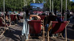 """Orang-orang menghadiri Cinema on the Water, yang diselenggarakan Paris Plages selama pemutaran """"Le Grand Bain"""" di Paris, Prancis pada 18 Juli 2020. Paris menghadirkan terobosan baru dengan bioskop terapung lengkap dengan perahu yang tetap menjaga jarak. (AP Photo/Rafael Yaghobzadeh)"""