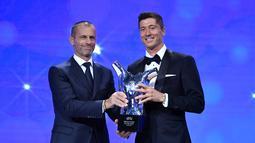 Penyerang Bayern Munchen, Robert Lewandowski menerima penghargaan Pemain Terbaik UEFA dari Presiden UEA Aleksander Ceferin dalam acara UEFA Awards di Genewa, Swiss (1/10/2020). (Harold Cunningham / AFP / UEFA)