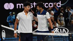 Petenis Korea Selatan Chung Hyeon berbincang usai mengalahkan petenis Serbia, Novak Djokovic pada putaran keempat kejuaraan tenis Australia Terbuka di Melbourne (22/1). Chung Hyeon menang 6-7(4), 5-7, 6-7(3). (AFP Photo/Paul Crock)
