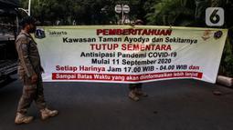 Petugas memasang spanduk pemberitahuan penutupan area kawasan Taman Ayodya, Jalan Bulungan dan Mahakam, Jakarta, Rabu (23/9/2020). Penutupan jalan dilakukan agar masyarakat tidak berkumpul di area itu pada waktu malam hari dan guna menekan angka penularan COVID-19. (Liputan6.com/Johan Tallo)