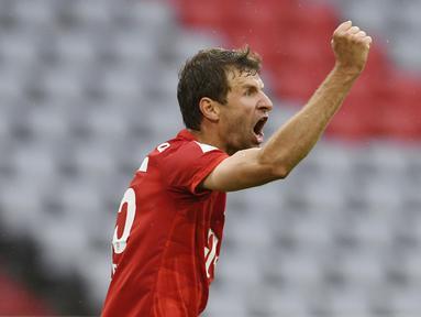 Pemain Bayern Munchen, Thomas Muller, melakukan selebrasi usai membobol gawang Eintracht Frankfurt pada laga Bundesliga di Allianz Arena, Minggu (24/5/2020). Bayern Munchen menang 5-2 atas Eintracht Frankfurt. (AP/Andreas Gebert)