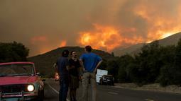 Warga berkumpul dan berbincang saat api membakar Hutan Nasional Angeles di California, Amerika Serikat, Rabu (12/8/2020). Kebakaran yang diberi nama Lake Fire tersebut terjadi di sekitar Danau Hughes. (AP Photo Ringo H.W. Chiu)
