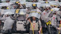 Hujan yang mengguyur di Ibukota tidak menyurutkan petugas kepolisian untuk tetap menjaga aksi Hari Buruh di Jalan Medan Merdeka, Jakarta, Senin (1/5). (Liputan6.com/ Yoppy Renato)