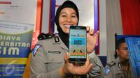 Petugas Kakorlantas Polri memperlihatkan aplikasi SIM Online saat launching di Jakarta, Jumat (16/12). Dalam rangka meminimalisir pungli, Korlantas merilis 3 aplikasi mulai dari SIM online, e-Tilang, hingga e-Samsat. (Liputan6.com/Angga Yuniar)