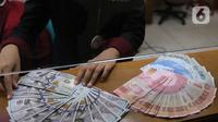 Petugas menunjukkan mata uang rupiah dan dolar di Jakarta, Senin (9/11/2020). Rupiah dibuka di angka 14.172 per dolar AS, menguat jika dibandingkan dengan penutupan perdagangan sebelumnya yang ada di angka 14.210 per dolar AS. (Liputan6.com/Angga Yuniar)