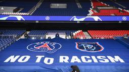 "Petugas stadion memasang spanduk raksasa bertuliskan ""NO TO RACISM"" menjelang laga lanjutan Liga Champions Grup H antara PSG melawan Istanbul Basaksehir di Parc des Princes Stadium, Selasa (8/12/2020). (AFP/Franck Fife)"