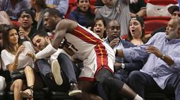 Guard Miami Heat, Dion Waiters terjatuh kearah penonton saat melawan Orlando Magic pada laga NBA preseason basketball game, di Miami (19/10/2016) WIB. (AP/Wilfredo Lee)