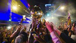 Tangan para fans LA Lakers berusaha menggapai trofi saat merayakan gelar juara NBA 2020 di Los Angeles, Senin (12/10/2020). LA Lakers menjuara NBA 2020 setelah mengalahkan Miami Heat dengan skor 106-93 dalam final gim ke enam. (AP Photo/Jintak Han)