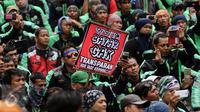 Pengemudi ojek on-line GrabBike mengangkat tulisan tuntutan saat unjuk rasa di belakang kantor Grab di kawasan Kuningan, Jakarta, Kamis (5/1). Mereka menuntut pihak perusahaan menaikkan tarif argo per kilometernya. (Liputan6.com/Helmi Fithriansyah)
