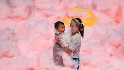 Seorang anak dan ibunya bermain busa yang dicampur dengan air cabai selama acara di daerah Ningxiang di provinsi Hunan tengah, China (2/7/2019). Acara ini diadakan untuk menarik wisatawan ke daerah terebut yang terkenal dengan makanan pedasnya. (AFP Photo/STR)