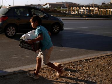 Seorang bocah penjual roti tradisional ketika menjajakan dagangannya di tepi jalan raya di pinggiran Algiers, Aljazair, 13 Juni 2016. Selama bulan Ramadan, sejumlah anak membantu orangtuanya menjajakan roti di kawasan ini. (REUTERS/Zohra Bensemra)