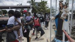 Para Migran Haiti berjalan menaiki perahu di Necocli, Kolombia, Rabu (28/7/2021). Ribuan migran terdampar di kota pelabuhan Kolombia saat mereka menunggu kapal menyeberang ke negara tetangga Panama dalam perjalanan mereka ke Amerika Serikat. (AP Photo/Ivan Valencia)