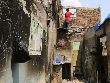 Warga merapikan rumahnya yang terdampak kebakaran di Jalan Prumpung Tengah RT 08/RW 05, Jakarta, Selasa (20/8/2019). Sebanyak 10 rumah hangus terbakar setelah kebakaran terjadi pada Senin, 19 Agustus 2019 sekira pukul 09.40 WIB. (Liputan6.com/Herman Zakharia)