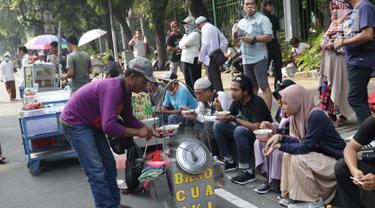 Pedagang asongan melayani pembeli yang mayoritas massa yang melakukan aksi di sekitaran Jalan Medan Merdeka Barat, Jakarta, Kamis (27/6/2019). Massa yang melakukan aksi terkait sidang putusan perselisihan hasil Pilpres 2019 memberi keuntungan bagi para pedagang. (Liputan6.com/Helmi Fithriansyah)