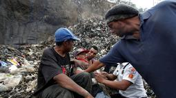 Seorang pemulung dihibur rekan-rekannya dan petugas pemadam kebakaran setelah sepupunya meninggal tertimpa longsoran ribuan kubik sampah di Tempat Pembuangan Akhir (TPA)  di Guatemala City, Guatemala, Rabu (27/4). (REUTERS/Josue Decavele)
