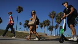 Seorang pria mengendarai Skuter listrik dari startup LimeBike di sepanjang Venice Beach, Los Angeles, 13 Agustus 2018. Anggota Dewan Los Angeles telah mengusulkan pelarangan skuter sampai peraturan dapat diselesaikan. (Mario Tama/Getty Images/AFP)