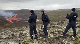 Penjaga Pantai Islandia memeriksa lava yang mengalir dari gunung berapi Fagradalsfjall yang meletus sekitar 40 km sebelah barat ibu kota Islandia, Reykjavik, pada Sabtu (20/3/2021). Sebuah gunung berapi di dekat ibu kota Islandia meletus pada hari Jumat, 19 Maret. (Icelandic Coast Guard via AP)