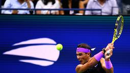 Petenis Spanyol, Rafael Nadal memukul bola ke arah lawannya petenis Argentina, Diego Schwartzman  pada babak perempat final AS Terbuka 2019  di Arthur Ashe Stadium, Rabu (4/9/2019). Nadal berhasil melangkah ke semifinal dalam pertarungan tiga set dengan skor 6-4, 7-5, dan 6-2. (Johannes EISELE/AFP)