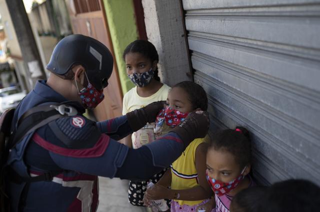 Petugas polisi militer Everaldo Pinto, berkostum superhero Captain America, memakaikan masker pada anak-anak di tengah pandemi COVID-19 di Petropolis, Rio de Janeiro, Brasil, Kamis (15/4/2021). Pinto memberitahu anak-anak tentang perlunya melindungi diri dari virus corona. (AP Photo/Silvia Izquierdo