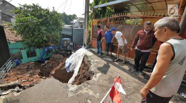 Sejumlah warga melihat saat alat berat membersihkan puing longsoran di Perumahan Pesona Kalisari, Pasar Rebo, Jakarta, Selasa (27/11). Intensitas hujan yang tinggi mengakibatkan sebidang tanah di wilayah tersebut longsor. (Liputan6.com/Herman Zakharia)
