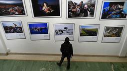 Pengunjung melihat foto karya fotografer Agence France-Presse (AFP) mengenai krisis migrasi di Eropa di pusat seni Bozar di Brussels (3/5). Pameran ini menampilkan foto-foto imigran dari Suriah, Irak sampai Turki dan Laut Tengah. (AFP Photo/John Thys)