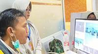 Petugas kesehatan sedang memindai suhu tubuh penumpang di Bandara DEO Sorong. (Kabarpapua/ Ist)
