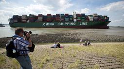 Seorang warga mengabadikan gambar kapal kontainer CSCL Jupiter Hong Kong yang terdampar di muara Westerschelde di dekat kota Bath di Belanda setelah insiden grounding (14/8).  (AFP PHOTO/Belga/Kristof Van Accom/Belgium Out)