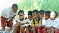 Salah seorang murid memperlihatkan buku baru di halaman sekolahnya di SD Negeri Inpres, Kleublouw, Kecamatan Sentani Timur, Kabupaten Jayapura, Papua.(Antara)