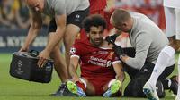 Petugas medis memeriksa bahu striker Liverpool, Mohamed Salah pada laga final Liga Champions di Stadion NSC Olimpiyskiy, Kiev, Minggu (27/5/2018). Salah mengalami cedera bahu usai dilanggar Ramos. (AP/Sergei Grits)