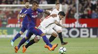 Pemain Barcelona, Paulinho Bezerra (kiri) mencoba melewati adangan pemain Sevilla, Banega pada laga La Liga Santander di Sanchez Pizjuan stadium, (31/3/2018). Barcelona bermain imbang 2-2 dengan Sevilla. (AP/Miguel Morenatti)