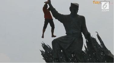 Seorang pria melakukan aksi tak wajar di atas patung Zapin yang berada di kawasan pusat kota Pekanbaru.