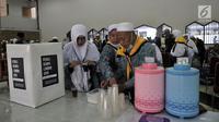 Jemaah haji membuat minuman yang disediakan PPIH saat tiba di Asrama Haji Pondok Gede, Jakarta, Kamis (29/8). (Merdeka.com/Iqbal S. Nugroho)